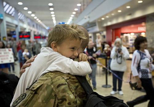 Lennie Mahler  |  The Salt Lake Tribune Witten Lundberg, 4, hugs his dad, Jared Lundbergy, at the Salt Lake City International Airport, Thursday, Nov. 21, 2013. Two pilots and four crew members of the Utah Army National Guard returned to Utah from a nine-month deployment to Afghanistan.