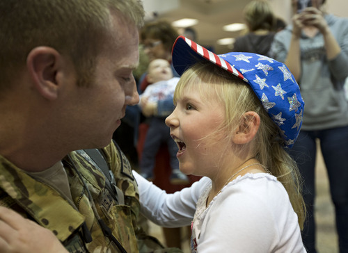 Lennie Mahler  |  The Salt Lake Tribune Shea Gillies embraces his daughter, Kylie, at the Salt Lake City International Airport, Thursday, Nov. 21, 2013. Two pilots and four crew members of the Utah Army National Guard returned to Utah from a nine-month deployment to Afghanistan.