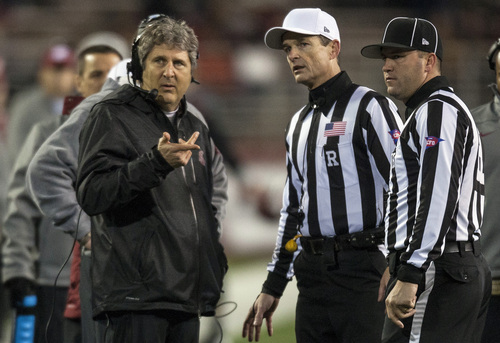 Washington State head coach Mike Leach, left, asks referee Land Clark, center, and head linesman Bart Longson, right, a question during the first half of an NCAA college football game against Arizona State, Thursday, Oct. 31, 2013, at Martin Stadium in Pullman, Wash. Arizona State won 55-21. (AP Photo/Dean Hare)