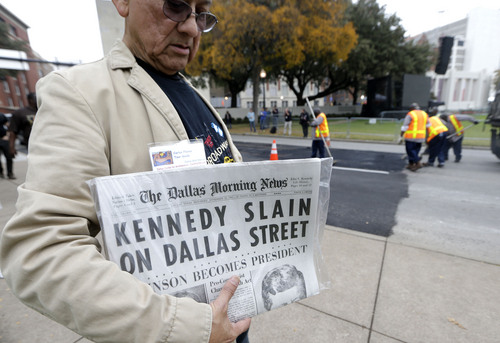 LM Otero     The Associated Press Carlos Flores holds a copy of the Dallas Morning News as work crews finish up street work on Dealey Plaza in Dallas, on Thursday. Loose gatherings of the curious and conspiracy-minded at Dallas' Dealey Plaza have marked past anniversaries of the assassination of President John F. Kennedy. But for the 50th anniversary, the city of Dallas has planned a solemn ceremony Friday in the plaza he was passing through when shots rang out. There will be brief remarks by the mayor and the tolling of church bells.