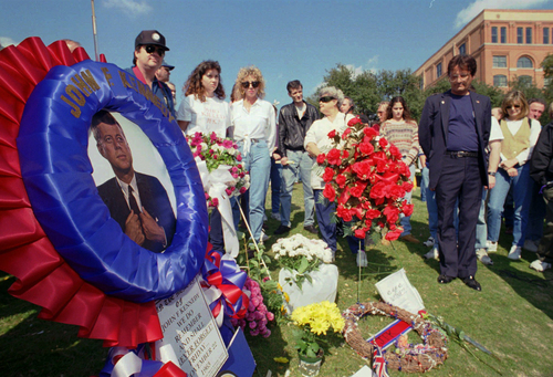 FILE - In this Nov. 22, 1995, file photo, people pause during a moment of silence at Dealey Plaza in Dallas, where President John F. Kennedy was assassinated.  Loose gatherings of the curious and conspiracy-minded have marked past anniversaries of the assassination of President Kennedy. But in the place where the president's motorcade passed through and shots rang out on Nov. 22, 1963, a solemn ceremony on the 50th anniversary of his death is designed to avoid such distractions, with  brief remarks by the mayor and the tolling of church bells. (AP Photo/Tim Sharp, File)