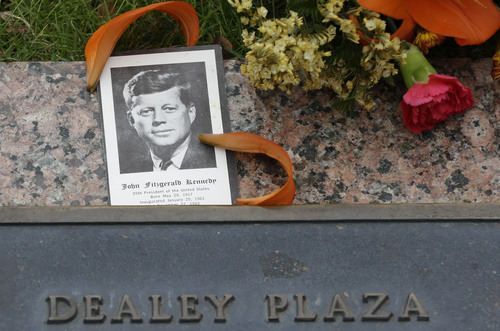 A photo of JKF and flowers lay on a plaque at Dealey Plaza in Dallas,  Thursday, Nov. 21, 2013.  Loose gatherings of the curious and conspiracy-minded at Dallas' Dealey Plaza have marked past anniversaries of the assassination of President John F. Kennedy. But for the 50th anniversary, the city of Dallas has planned a solemn ceremony Friday in the plaza he was passing through when shots rang out. There will be brief remarks by the mayor and the tolling of church bells.  (AP Photo/LM Otero)