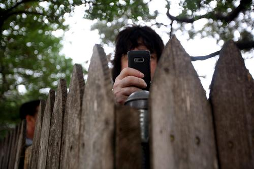 FILE - In this Nov. 22, 2008, file photo, an observer takes a picture with his cell phone from behind the wooden fence on top of the grassy knoll at Dealey Plaza in Dallas, at the 45th anniversary of the assassination of President John F. Kennedy. Loose gatherings of the curious and conspiracy-minded have marked past anniversaries of the assassination of President Kennedy. But in the place where the president's motorcade passed through and shots rang out on Nov. 22, 1963, a solemn ceremony on the 50th anniversary of his death is designed to avoid such distractions, with  brief remarks by the mayor and the tolling of church bells. (AP Photo/The Dallas Morning News, Lara Solt) **MANDATORY CREDIT, NO SALES, MAGS OUT, TV OUT, INTERNET OUT, AP MEMBERS ONLY**