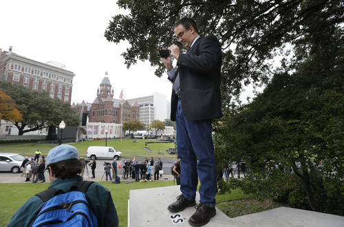 Gilbert Guindon of Quebec City, Canada, stands and makes photos on the spot where the Zapruder film was made overlooking Dealey Plaza in Dallas, Thursday, Nov. 21, 2013.  Loose gatherings of the curious and conspiracy-minded at Dallas' Dealey Plaza have marked past anniversaries of the assassination of President John F. Kennedy. But for the 50th anniversary, the city of Dallas has planned a solemn ceremony Friday in the plaza he was passing through when shots rang out. There will be brief remarks by the mayor and the tolling of church bells.  (AP Photo/LM Otero)