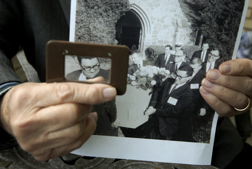 Mike Cochran poses holding a photo Friday, Nov. 15, 2013, at his home in Haltom City, Texas, using a magnifying glass to highlight his face along with other reporters serving as pallbearers. On a gloomy November afternoon, I helped carry the inexpensive wooden casket of Lee Harvey Oswald to a grave on a slight rise dotted with dying grass. (AP Photo/Tony Gutierrez)