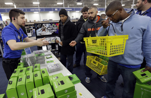 Nikolai Vacca, left, explains newest XBox One accessories to customers at a Best Buy store on Friday, Nov. 22, 2013., in Evanston, Ill. The Xbox One, which includes an updated Kinect motion sensor, cost $500. Microsoft is billing it as an all-in-one entertainment system rather than just a gaming console. (AP Photo/Nam Y. Huh)