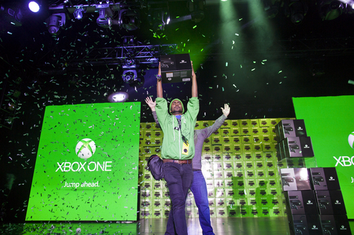 One of the first ten people to purchase the Microsoft Xbox One game system exalts in the moment at an event as they receive their equipment in New York Friday, Nov. 22, 2013.  Xbox One is a new all-in-one games and entertainment system from Microsoft. (AP Photo/Craig Ruttle)