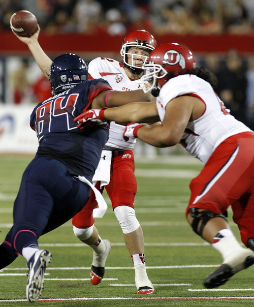 Utah's quarterback Adam Schulz (in back) throws over the Arizona rush in the second half of an NCAA collge football game, Saturday, Oct. 19, 2013 in Tucson, Ariz. Arizona won 35 to 24. (AP Photo/John Miller)
