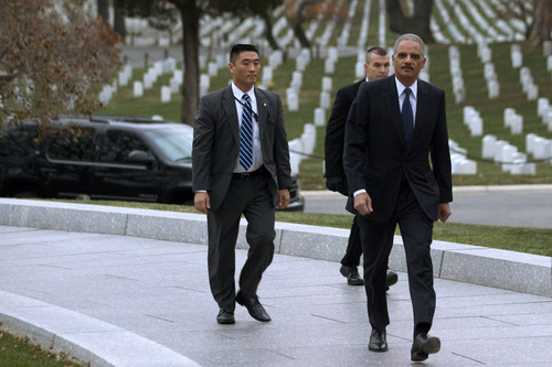 Attorney General Eric Holder, right, arrives to pay his respects at the grave of John F. Kennedy at Arlington National Cemetery on Friday, Nov. 22, 2013, on the 50th anniversary of Kennedy's death. Holder has been visiting the grave since his youth, and would visit there with his mother before she passed away. (AP Photo/Jacquelyn Martin)