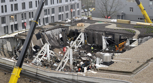 A  view of collapsed Maxima supermarket in Riga, Latvia, Friday, Nov. 22, 2013. At least 32 people died, including three firefighters, after an enormous section of roof collapsed at a Latvian supermarket in the country's capital, emergency medical officials said Friday. The reason for the collapse during shopping rush-hour Thursday was still not known but rescue and police officials said that possible theories include building's design flaws and poor construction work. (AP Photo/ Roman Koksarov)