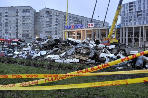 Debris, foreground,which was removed by rescue teams during a search for victims at the Maxima supermarket in Riga, Latvia, Friday, Nov. 22, 2013. At least 32 people died, including three firefighters, after an enormous section of roof collapsed at a Latvian supermarket in the country's capital, emergency medical officials said Friday. The reason for the collapse during shopping rush-hour Thursday was still not known but rescue and police officials said that possible theories include building's design flaws and poor construction work. (AP Photo/ Roman Koksarov)