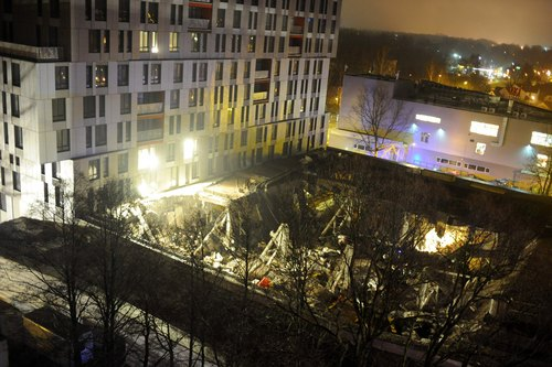 A  late Thursday, Nov. 21, 2013 view of the collapsed Maxima supermarket in Riga, Latvia. At least 32 people died, including three firefighters, after an enormous section of roof collapsed at a Latvian supermarket in the country's capital, emergency medical officials said Friday. The reason for the collapse during shopping rush-hour Thursday was still not known but rescue and police officials said that possible theories include building's design flaws and poor construction work. (AP Photo/ Maris Morkans)