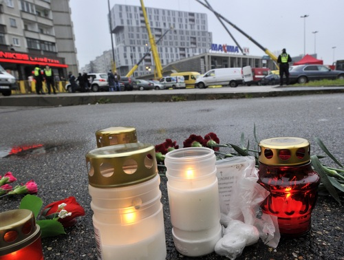Candles and flowers outside the collapsed Maxima supermarket in Riga, Latvia, Friday, Nov. 22, 2013. At least 32 people died, including three firefighters, after an enormous section of roof collapsed at a Latvian supermarket in the country's capital, emergency medical officials said Friday. The reason for the collapse during shopping rush-hour Thursday was still not known but rescue and police officials said that possible theories include building's design flaws and poor construction work. (AP Photo/ Roman Koksarov)