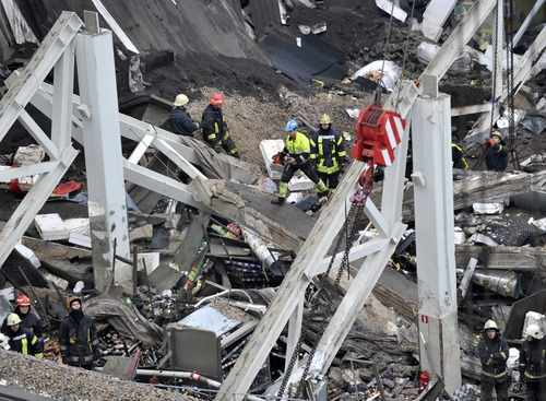 Rescue workers search debris of the Maxima supermarket in Riga, Latvia, Friday, Nov. 22, 2013. At least 32 people died, including three firefighters, after an enormous section of roof collapsed at a Latvian supermarket in the country's capital, emergency medical officials said Friday. The reason for the collapse during shopping rush-hour Thursday was still not known but rescue and police officials said that possible theories include building's design flaws and poor construction work. (AP Photo/ Roman Koksarov)