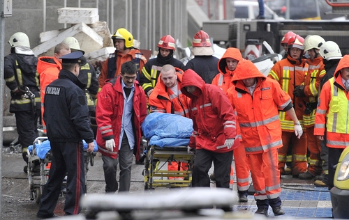 Rescue workers carry a stretcher with a victim outside the Maxima supermarket in Riga, Latvia, Friday, Nov. 22, 2013. At least 32 people died, including three firefighters, after an enormous section of roof collapsed at a Latvian supermarket in the country's capital, emergency medical officials said Friday. The reason for the collapse during shopping rush-hour Thursday was still not known but rescue and police officials said that possible theories include building's design flaws and poor construction work. (AP Photo/ Roman Koksarov)
