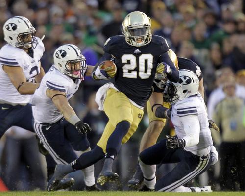 Notre Dame running back Cierre Wood, center, cuts between Brigham Young defenders Spencer Hadley, left, Daniel Sorensen, left center, and Joe Sampson during the second half of an NCAA college football game in South Bend, Ind., Saturday, Oct. 20, 2012. Notre Dame defeated BYU 17-14. (AP Photo/Michael Conroy)