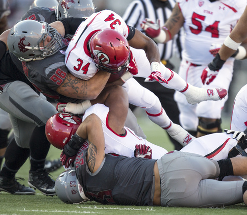 Washington State defensive lineman Xavier Cooper (96) tackles Utah running back Bubba Poole (34) during the first half of an NCAA college football game on Saturday, Nov. 23, 2013, in Pullman, Wash. (AP Photo/Dean Hare)