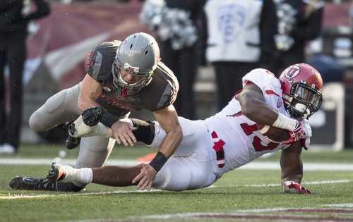 Utah running back Kelvin York (13) scores a touchdown through the tackle attempt of Washington State safety Casey Locker (22) during the first half of an NCAA college football game Saturday, Nov. 23, 2013, at Martin Stadium in Pullman, Wash. (AP Photo/Dean Hare)