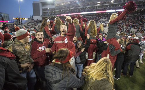 Washington State fans rush the field after their team defeated Utah 49-37 in an NCAA college football game on Saturday, Nov. 23, 2013, in Pullman, Wash. (AP Photo/Dean Hare)