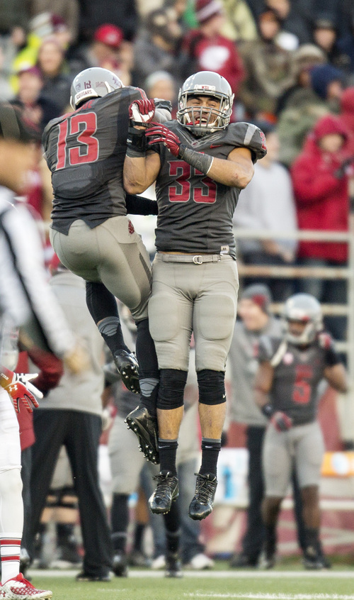 Washington State linebackers Tana Pritchard (33) and Darryl Monroe (13) celebrate after forcing Utah to punt during the second half of an NCAA college football game on Saturday, Nov. 23, 2013, in Pullman, Wash. Washington State won 49-37.(AP Photo/Dean Hare)