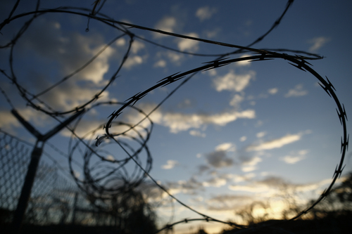 In this photo reviewed by the U.S. military, concertina wire hangs off a fence in the now abandoned Camp X-Ray, which was used as the first detention facility for al-Qaida and Taliban militants who were captured after the Sept. 11 attacks at Guantanamo Bay Naval Base, Cuba, Thursday, Nov. 21, 2013.  Detainees were housed in open air pens until the completion of Camp Delta in April 2002. (AP Photo/Charles Dharapak)