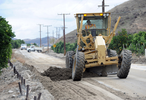Road crews work to scrape away mud along San Timoteo Canyon Road on Friday, Nov. 22, 2013, in Redlands, Calif., the day after after heavy rains hit the area causing the road to flood. (AP Photo/The Redlands Daily Facts, John Valenzuela)