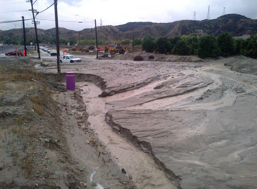 This Nov. 21, 2013 photo released courtesy City of Redlands shows flooding, mud and debris on San Timoteo Canyon Road in Redlands, Calif. Firefighters responded to dozens of calls of weather-related traffic collisions, flooding and mudslides spurred by Thursday's downpour in southern California. (AP Photo/City of Redlands)