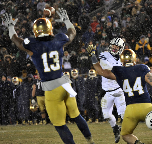 Brigham Young quarterback Taysom Hill throws a pass which is knocked down by Notre Dame linebacker Jaylon Smith, left, in the second half of an NCAA college football game Saturday, Nov. 23, 2013, in South Bend, Ind. Notre Dame won 23-13.  (AP Photo/Joe Raymond)