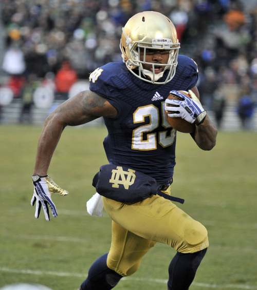 Notre Dame running back Tarean Folston heads to the end zone with a touchdown in the first half of an NCAA college football game Saturday, Nov. 23, 2013, in South Bend, Ind. (AP Photo/Joe Raymond)