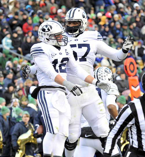 Brigham Young wide receiver JD Falsely, left, and offensive lineman De' Ondre Wesley chest bump after Falsely scored a BYU touchdown in the first half of an NCAA college football game Saturday, Nov. 23, 2013, in South Bend, Ind. (AP Photo/Joe Raymond)