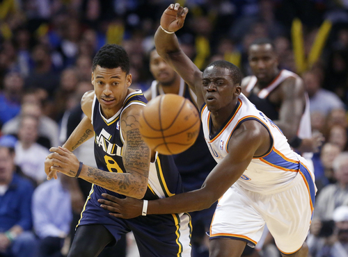 Utah Jazz guard Diante Garrett (8) and Oklahoma City Thunder guard Reggie Jackson chase a loose ball in the second quarter of an NBA basketball game in Oklahoma City, Sunday, Nov. 24, 2013. (AP Photo/Sue Ogrocki)