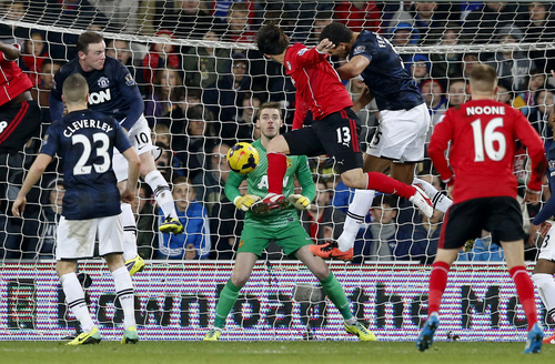 Cardiff City's Kim Bo-Kyung, center 13, scores his side's second goal to equalize the game 2-2 during the English Premier League soccer match between Manchester United and Cardiff City at Cardiff City Stadium in Cardiff, Wales, Sunday, Nov. 24, 2013.  (AP Photo/Matt Dunham)