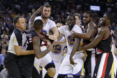 Portland Trail Blazers' Mo Williams, left, is restrained by a referee as he fights with Golden State Warriors' Andrew Bogut (12) during the second half of an NBA basketball game Saturday, Nov. 23, 2013, in Oakland, Calif. Trail Blazers Wesley Matthews (2), right, Mo Williams (25), and Warriors' Draymond Green (23) were ejected from the game. (AP Photo/Ben Margot)