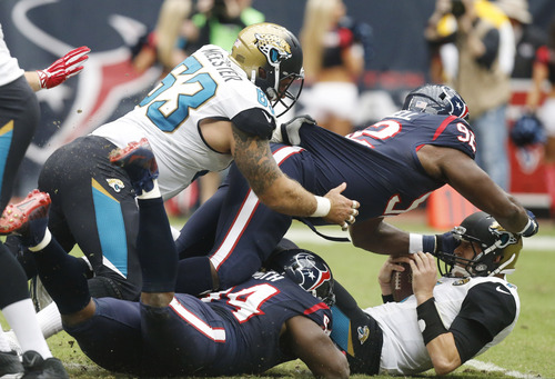 Jacksonville Jaguars quarterback Chad Henne gets sacked by Houston Texans nose tackle Earl Mitchell (92) during the first quarter an NFL football game Sunday, Nov. 24, 2013, in Houston. (AP Photo/Patric Schneider)