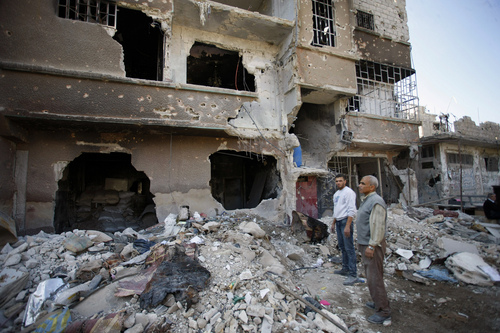 In this photo taken Wednesday, Nov. 20, 2013 Syrian civilians inspect their home destroyed during clashes between the Sunni-dominated Free Syrian Army and Syrian soldiers loyal to Syria's President Bashar Assad, supported by Iraqi and Lebanese Shiite fighters, in the town of Hejeira, which Syrian troops captured, in the countryside of Damascus, Syria. (AP Photo/Jaber al-Helo)
