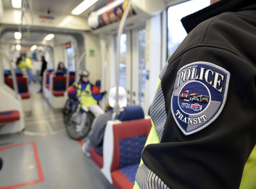 Al Hartmann  |  The Salt Lake Tribune UTA police officers can be seen in their distinctive black and safety green colors along the TRAX line.  They want to be obvious to riders and public believing that their visibility actually keeps crime from happening.