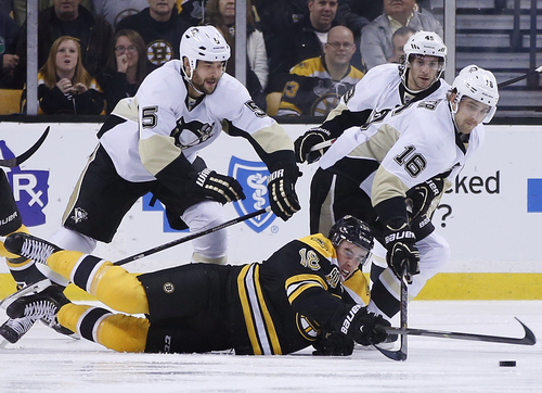 Boston Bruins right wing Reilly Smith (18) dives in an attempt to control the puck against Pittsburgh Penguins defenseman Deryk Engelland (5), center Brian Gibbons (49) and center Brandon Sutter (16) in the first period of an NHL hockey game in Boston, Monday, Nov. 25, 2013. (AP Photo/Elise Amendola)