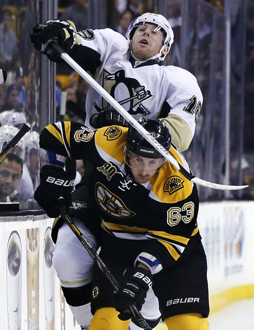 Pittsburgh Penguins left wing James Neal (18) crashes into Boston Bruins left wing Brad Marchand (63) along the boards in the third period of an NHL hockey game in Boston, Monday, Nov. 25, 2013. The Bruins won 4-3 in overtime. (AP Photo/Elise Amendola)
