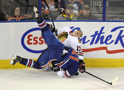 Chicago Blackhawks' Sheldon Brookbank (17) gets knocked down by Edmonton Oilers' Will Acton (41)  during the first period of an NHL hockey game in Edmonton, Alberta, on Monday, Nov. 25, 2013. (AP Photo/The Canadian Press, John Ulan)