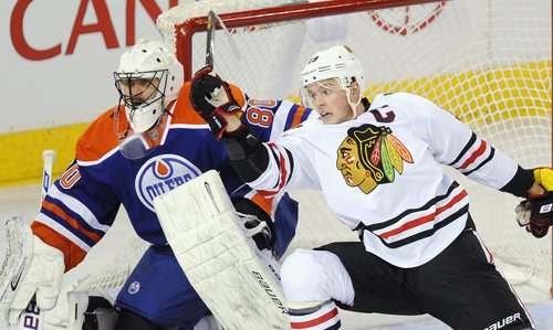 Edmonton Oilers goalie Ilya Bryzgalov (80) and Chicago Blackhawks Jonathan Toews (19) work in front of the net during the second period of an NHL hockey game in Edmonton, Alberta, on Monday, Nov. 25, 2013. (AP Photo/The Canadian Press, John Ulan)