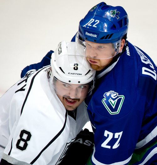 Los Angeles Kings' Drew Doughty, left, and Vancouver Canucks' Daniel Sedin, of Sweden, battle for position in front of the Kings' net during the second period of an NHL hockey game, in Vancouver, British Columbia, Monday Nov. 25, 2013. (AP Photo/The Canadian Press, Darryl Dyck)