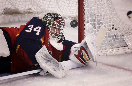 Florida Panthers goalie Tim Thomas (34) stops a shot on goal by a Philadephia Flyers player during the first period of the NHL hockey game in Sunrise, Fla., Monday, Nov. 25, 2013. (AP Photo/J Pat Carter)