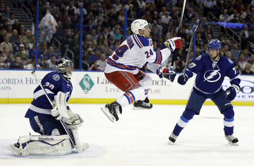 New York Rangers right wing Ryan Callahan (24) leaps into the air in an attempt to screen Tampa Bay Lightning goalie Ben Bishop (30) during the first period of an NHL hockey game Monday, Nov. 25, 2013, in Tampa, Fla. Defending for Tampa Bay is Victor Hedman (77), of Sweden. (AP Photo/Chris O'Meara)