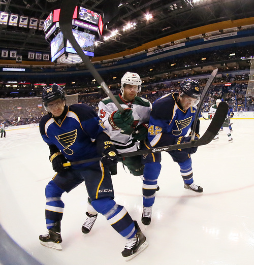 Minnesota Wild right wing Jason Pominville, center, is double-teamed by St. Louis Blues left wing Alexander Steen,k left, and center David Backes during the second period of an NHL hockey game Monday, Nov. 25, 2013, in St. Louis. (AP Photo/St. Louis Post-Dispatch, Chris Lee) EDWARDSVILLE OUT  ALTON OUT