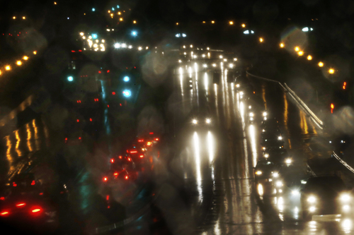 Reflected in the driver side mirror, motorists drive in the rain on Montrose Road in Rockville, Md., towards Interstate 270 out of Washington, Tuesday, Nov. 26, 2013, two days before the Thanksgiving holiday. (AP Photo/Charles Dharapak)
