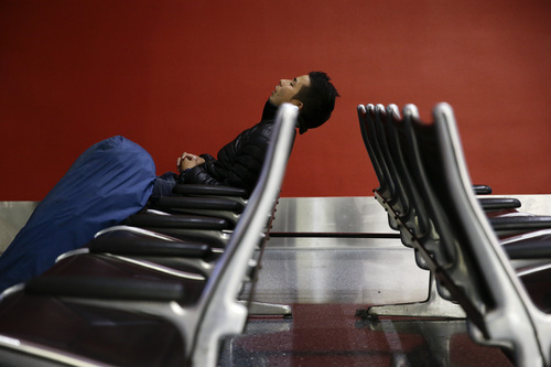 A man sleeps at the Los Angeles International Airport on Wednesday, Nov. 27, 2013, in Los Angeles. More than 43 million people are to travel over the long holiday weekend, according to AAA. (AP Photo/Jae C. Hong)