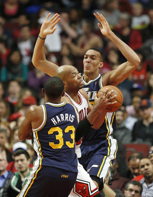 Chicago Bulls forward Taj Gibson, center, goes to the basket between Utah Jazz forward Mike Harris, left, and Utah Jazz center Rudy Gobert, right, during the fourth quarter of an NBA basketball game in Chicago, Friday, Nov. 8, 2013. Bulls won 97-73. (AP Photo/Kamil Krzaczynski)