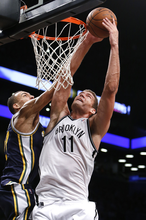 Brooklyn Nets' Brook Lopez (11) goes to the basket against Utah Jazz's Rudy Gobert during the second half of an NBA basketball game Tuesday, Nov. 5, 2013, in New York. Brooklyn won 104-88. (AP Photo/Jason DeCrow)