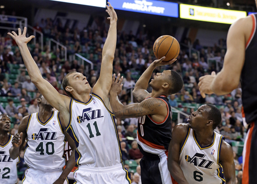 Portland Trail Blazers' Damian Lillard (0) shoots as Utah Jazz's Andris Biedrins (11) defends while Utah'sLester Hudson (6) watches duringthe second quarter of an NBA preseason basketball game Wednesday, Oct. 16, 2013, in Salt Lake City. (AP Photo/Rick Bowmer)
