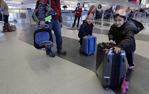 With turkey themed hats, 5-year-old Rishi, and 3-year-old Ravi Chandra wheel their suitcases through terminal three Wednesday, Nov. 27, 2013, at O'Hare International airport in Chicago as they head to Austin, Texas with their parents. While the morning commute at O'Hare is running smoothly, a wall of storms packing ice, sleet and rain heading for the east coast and the north east could upend holiday travel plans as millions of Americans take to the roads, skies and rails Wednesday for Thanksgiving. (AP Photo/M. Spencer Green)
